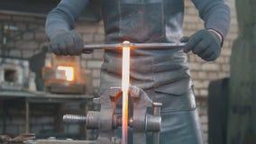 Zakończenie w górę widoku - ręki Blacksmith z rękawiczkami w kuźni robią stalowemu nożowi fotografia royalty free