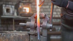 Zakończenie w górę widoku - ręki Blacksmith z rękawiczkami w kuźni robią stalowemu nożowi zdjęcie royalty free