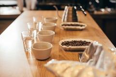 zakończenie w górę widoku ustaweni puchary z kawowymi fasolami i zgrzytnięcie kawą dla karmowej funkci fotografia royalty free