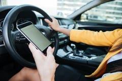 Zakończenie w górę wizerunku z żeńskim kierowcą i pustym telefonu ekranem zdjęcia stock