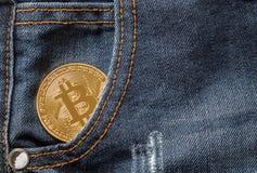 Zakończenie w górę złotego bitcoin w drelichowych cajgach wkładać do kieszeni obraz stock