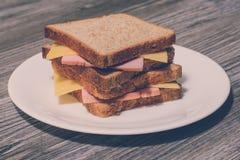 Zakończenie w górę zasięrzutnego fotografia obrazka wysoki smakowity yummy wyśmienicie z serem i saussage kanapką na rount talerz obrazy royalty free