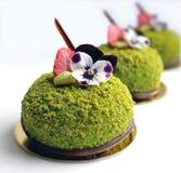 Zakończenie w górę zieleni textured pistacjowych desery z jadalnymi pansy kwiatami i suszył truskawki fotografia royalty free