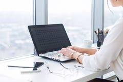 Zakończenie widok żeński urzędnik pisać na maszynie, pracuje z nowym projektem przy jej miejscem pracy, używać laptop i fi Fotografia Royalty Free