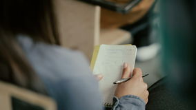 Zakończenie widok żeńskie ręki Kobiety obsiadanie na writing w notatniku i krześle Uczeń opowiada z ludźmi przy wykładem zbiory
