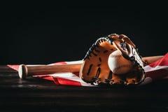 zakończenie widok baseball rękawiczka z piłką i nietoperzem na drewnianym stole i nas chorągwianych obraz stock