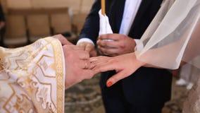 Zakończenie widok ksiądz wręcza stawiać obrączki ślubne na rękach nowożeńcy panny młodej ceremonii kwiatu ślub zdjęcie wideo