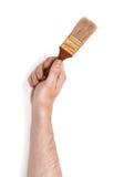 Zakończenie widok man& x27; s ręka z farby muśnięciem, odosobnionym na białym tle Zdjęcia Royalty Free