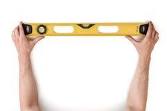 Zakończenie widok man& x27; s ręki trzyma żółtego budynku poziom odizolowywający na białym tle Zdjęcie Royalty Free