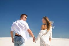 Zakończenie widok od z powrotem szczęśliwe pary mienia ręki na białym piaska tle obrazy royalty free