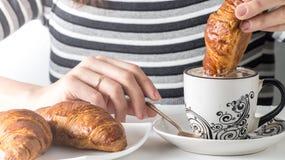 Zakończenie widok ręka zamacza croissant w kawie Obrazy Royalty Free