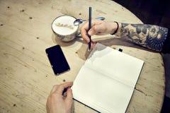 Zakończenie widok samiec ręki z nutową książką i kawowym odgórnym widokiem Zdjęcia Royalty Free