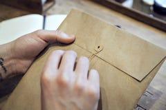 Zakończenie widok samiec wręcza trzymać brown kopertę z kawą przy drewnianym biurkiem Obrazy Royalty Free