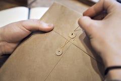 Zakończenie widok samiec wręcza trzymać brown kopertę z kawą przy drewnianym biurkiem Obrazy Stock