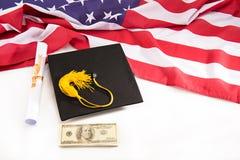 Zakończenie widok skalowania mortarboard, dyplom, dolarowi banknoty i my chorągwiani na bielu, zdjęcia stock
