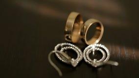 Zakończenie widok złote obrączki ślubne srebni bridal kolczyki z diamons przy stołem i zbiory