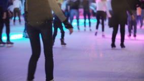 Zakończenie widok zatłoczony miejsce, młodzi człowiecy i kobiety na lodzie z barwionym światłem jeździć na łyżwach wpólnie, zdjęcie wideo