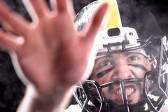 Zakończenie widoku agresywny mężczyzna w hełmie bawić się futbol amerykańskiego Zdjęcia Royalty Free