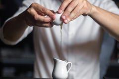 Zakończenie wizerunek barman wręcza łamać jajko w mleko p fotografia stock