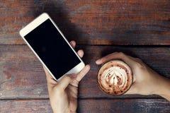 Zakończenie wizerunek kobieta lub samiec wręcza używać smartphone przy kawiarnią w obrazy stock