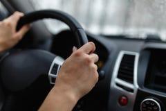 Zakończenie woman& x27; s ręka trzyma kierownicę Dziewczyna kierowca r Obraz Royalty Free