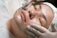 Zakończenie Wschodnia dziewczyna na procedurze czyścić skóra w piękno salonie Ręki fachowy beautician w rękawiczce zdjęcia stock