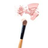 Zakończenie zdruzgotanego kopalnego shimmer proszka złoty kolor z makeup muśnięciem na białym tle Obrazy Stock