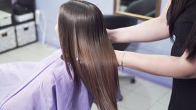 Zakończenie zwolnione tempo strzelający tylni widok fryzjer ocenia rezultat prostować włosy z keratyną, wydaje zdjęcie wideo