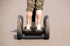 Zakończenia up tylna istota ludzka na Airwheel Elektrycznym Unicycle w drodze Fotografia Stock