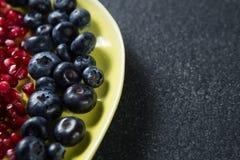 Zakończenie czarne jagody z granatowów ziarnami w talerzu Obrazy Stock