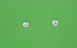 Zakończenie dwa nitu w deski zieleni teksturze Fotografia Stock