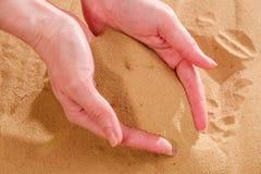 Zako?czenie ?e?ski r?ki laszowanie opuszcza piasek Piaska sp?ywanie przez r?k zdjęcie royalty free