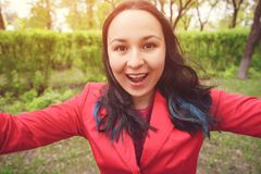 Zako?czenie fotografia Młoda kobieta w czerwieni ubraniach na ulicie bierze selfie, spojrzenia przy kamerą i uśmiechy, zdjęcie royalty free
