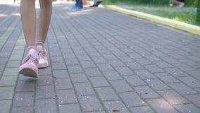 Zako?czenie kobiet nogi w eleganckich r??owych sneakers dziewczyny odprowadzenie na ulicie z brukiem Naturalny pogodny ?wiat?o dz zbiory
