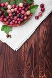 Zakończenie obrazek dojrzali jaskrawi czerwoni agresty w koszu na szarej torbie drewnianym stole i Obraz Royalty Free