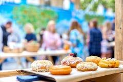 Zakończenie smakowici piec donuts z glazurowaniem i jagody w sunli Obrazy Royalty Free