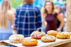Zakończenie smakowici piec donuts z glazurowaniem i jagody w sunli Zdjęcia Stock