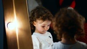 Zako?czenie strza? Mała dziewczynka stojaki przy lustrem nieśmiałymi spojrzeniami i trochę zdjęcie wideo
