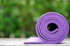 Zakończenie up purpurowa joga mata na stole Fotografia Royalty Free
