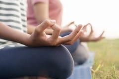 Zako?czenie w g?r? r?ki i po??wki cia?a zdrowie kobiety siedzi w lotosowej joga pozycji w ranku przy parkiem ?wiczy? joga robi me zdjęcie royalty free
