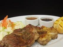 Zakończenie, wieprzowina stek z czarnym pepper& x28; odizolowywa na black& x29; Zdjęcie Stock