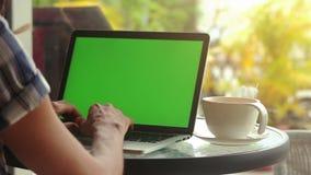 Zakończenie samiec wręcza używać laptop przy kawiarnią z zieleń ekranem zdjęcie wideo