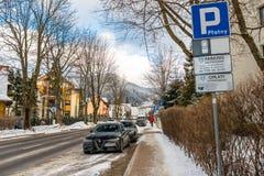 Zakopane, Polônia - 22 de fevereiro de 2019 Estacionamento na rua na cidade, construções urbanas visíveis, sinais que informam so fotos de stock royalty free