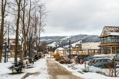 Zakopane, Poland - February 22, 2019. Park in the city covered with snow, visible sidewalk, cars in the parking lot and urban buil. Dings. In the background royalty free stock image