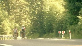 ZAKOPANE, POLAND - JUNE 24, 2017. Two cheerful adult male bicycle tourists climbing up the mountain asphalt road. Hot. ZAKOPANE, POLAND - JUNE 24, 2017. Two stock footage