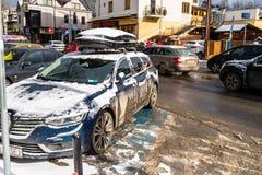 Zakopane Polen - Februari 22, 2019 Ett smutsigt och snö-täckt bilanseende i en parkeringsplats på en upptagen stads- väg Foto som arkivbilder