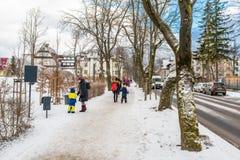 Zakopane, Polonia - 22 febbraio 2019 Turisti con i piccoli bambini che camminano lungo una strada nevosa, le automobili visibili, fotografia stock libera da diritti