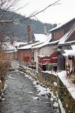 Zakopane town during the snowing, trees, fences and old houses along the mountain stream royalty free stock images