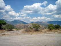 Zakrywający z zielonymi krzaków wzgórzami na Pogodnym gorącym dniu fotografia royalty free