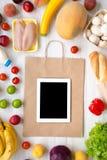 Zakupów sklepów spożywczych pojęcie Karmowa torba i różnorodny zdrowy jedzenie z pastylką na białym drewnianym stole Kulinarny ka obraz royalty free